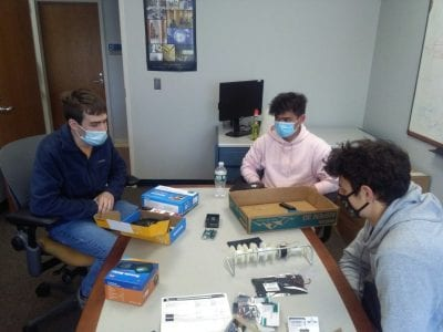 High-school students Kai and Dar discussing their project ideas with electrical engineering undergraduate student Kevin