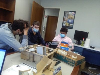 High-school students Kai and Dar duscussing their project ideas with electrical engineering undergraduate student Kevin
